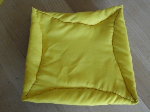 Quilted square, yellow with red thread